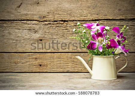 wood texture with watering cans decorated with flowers