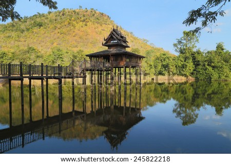 wood Thai pavilion reflect in pool with mountain and blue sky