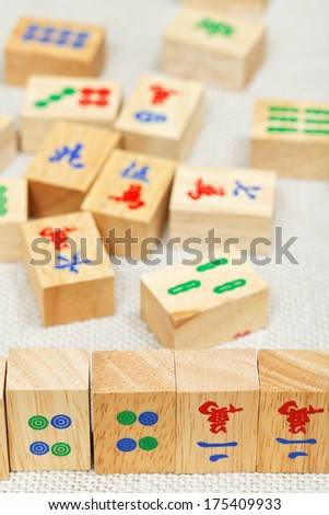 wood tiles closeup in mahjong game during playing on textile table