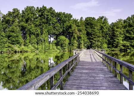 Wood walkway leads over a swamp in Alabama - stock photo
