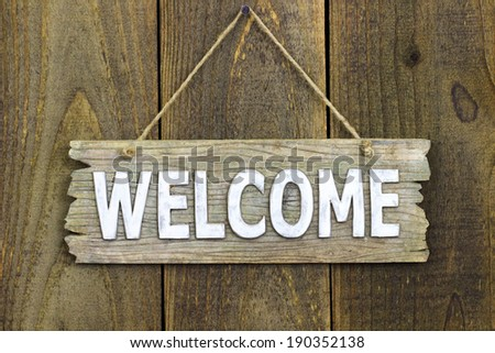 Wood welcome sign hanging on rustic wooden background - stock photo