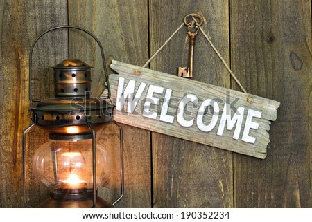 Wood welcome sign hanging on wooden background by glowing antique lantern - stock photo