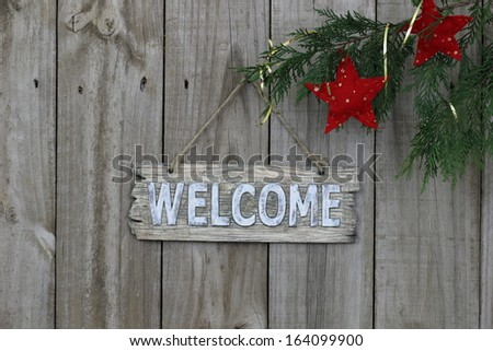 Wood welcome sign on fence with red stars hanging from tree - stock photo