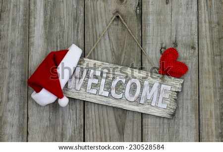 Wood welcome sign with Christmas Santa Claus hat and red heart hanging on rustic wooden background - stock photo