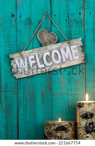 Wood welcome sign with heart and burning candles hanging on antique teal blue weathered wooden background - stock photo