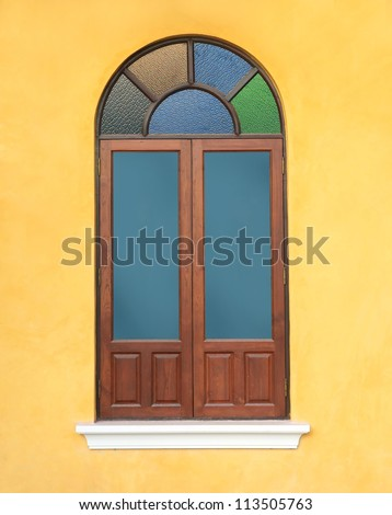 wood window with colorful glass on yellow wall