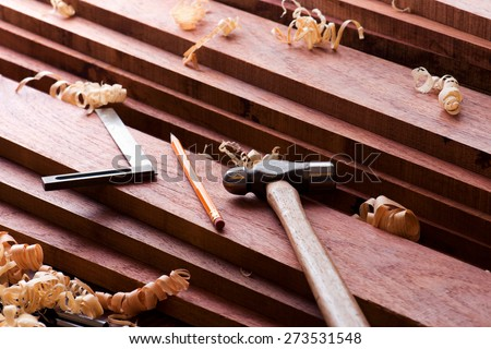 Wood working. Fine quality hardwood lumber, ready for use. pencil, square rule , and a hammer on lumber. - stock photo