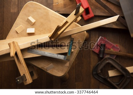 Wood working project. Camp clamps holding pieces of wood with square edge ruler. Focus in on square edge ruler. Shot in low key and shallow depth of field. - stock photo