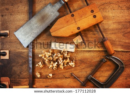 Wood working. Saw, clamps and wood shavings on a work desk under incandescent light.  - stock photo