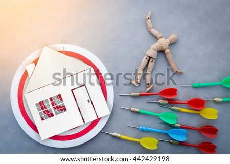 woode figure is aimming dartboard with house paper cut - stock photo
