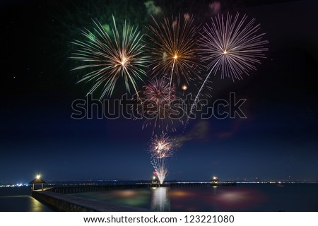 Wooded bridge in the port between new year celebration with firework. - stock photo