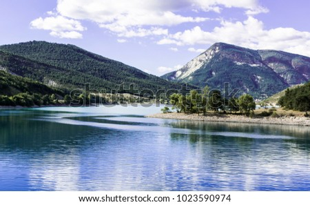 Wooded shore of the lake in French Alps. Lake Castillon is a reservoir in Alpes-de-Haute-Provence in France.
