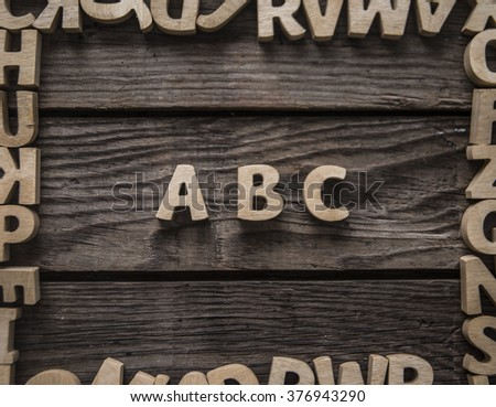 Wooden ABC letter in frame alphabet on the wooden background - stock photo