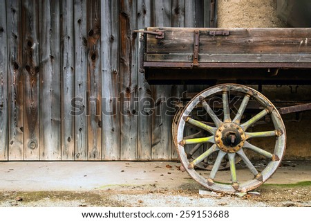 wooden agriculture trailer with spoke wheel in front of a barn