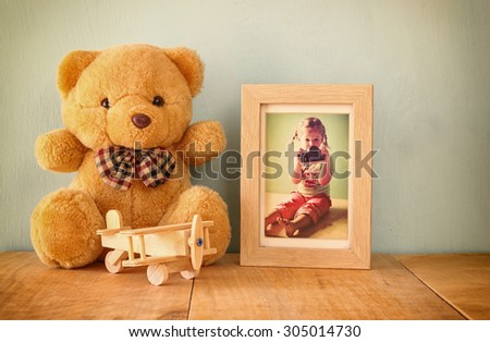 wooden airplane toy and teddy bear over wood table next to photo frame with kid's old photography. retro filtered image  - stock photo