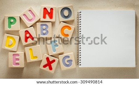 Wooden alphabet blocks with letters on brown paper background