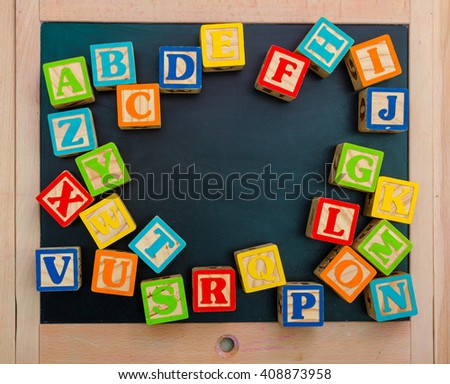 Wooden alphabet blocks with letters on wooden board - stock photo
