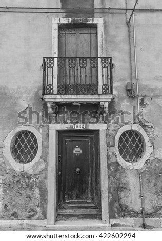 Wooden Ancient Italian Door in Historic Center . Black and white photography. - stock photo