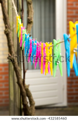 Wooden and plastic clothespins on a clothes line. Bright colors.