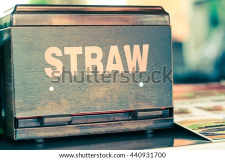 Wooden and Plastic Drinking Straw Box, Food Menu Beside, on Reception Counter Table at Cafe or Fast Food Restaurant. Very Shallow Focus. Vintage and Retro Effect.