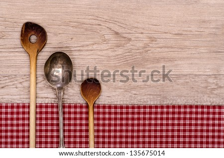 Wooden and silver spoon on a wooden board with text space - stock photo