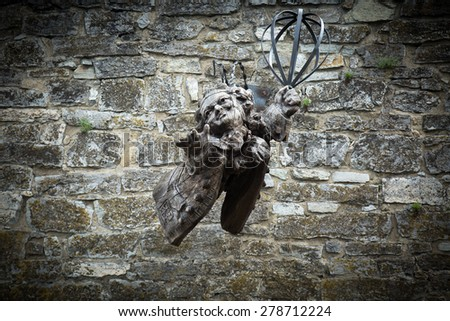 wooden angel statue on stone wall - stock photo