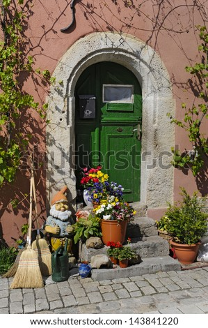 wooden antique door in germany decorated with flowers and gnome - stock photo