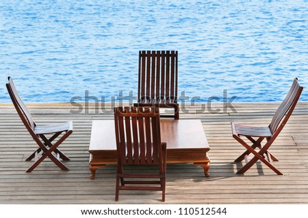 Wooden area with chairs and table on calm blue water - stock photo