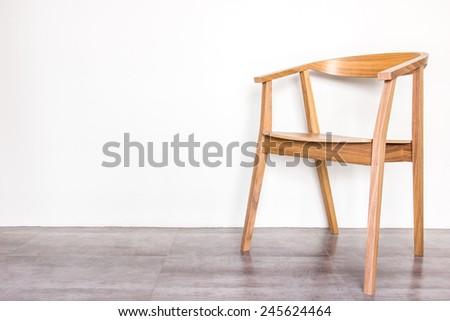 wooden armchair on gray tile floor and warm background - stock photo