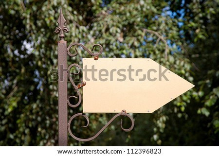 Wooden arrow cursor on a metal pole. Ready for your labels, logo or symbol.