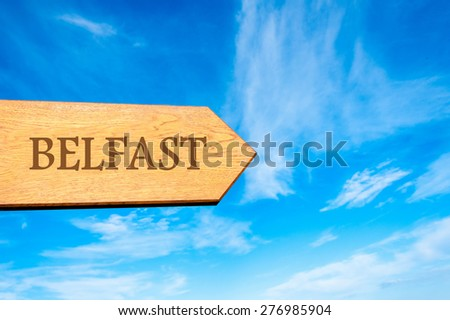 Wooden arrow sign pointing destination BELFAST, NORTHERN IRELAND against clear blue sky with copy space available. Travel destination conceptual image - stock photo