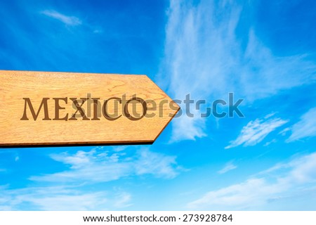 Wooden arrow sign pointing destination MEXICO against clear blue sky with copy space available. Travel destination conceptual image - stock photo