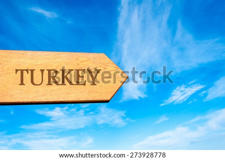 Wooden arrow sign pointing destination TURKEY against clear blue sky with copy space available. Travel destination conceptual image - stock photo