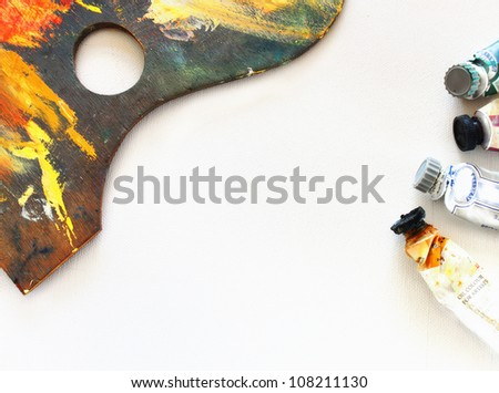 wooden art palette and paints over canvas - stock photo