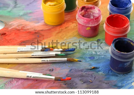 wooden art palette with paint and brushes, close up - stock photo