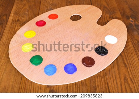 Wooden art palette with paint on table close-up