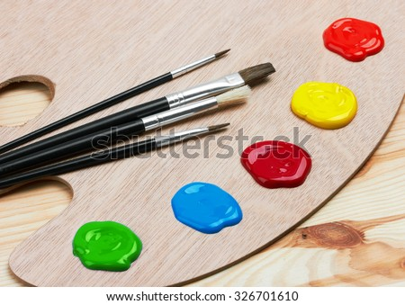 Wooden art palette with paints and brushes, on wooden background - stock photo
