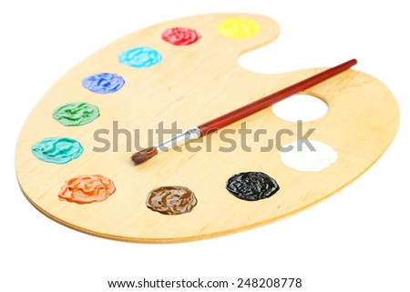 Wooden art palette with paints isolated on white - stock photo
