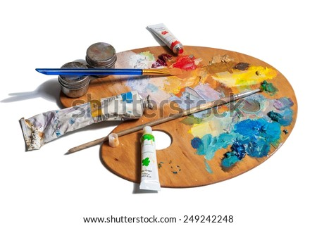 Wooden art palette with tubes of oil paints and a brushes isolated on white background