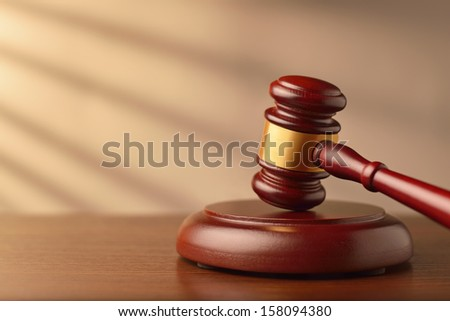 Wooden auctioneer or judges gavel for dispensing justice or knocking down sale prices against a background with rays of sunlight and shadow