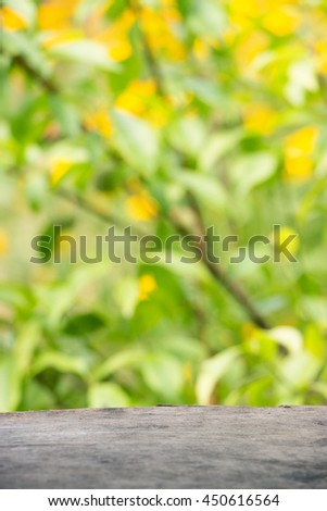 Wooden background against the backdrop of bright yellow-green flowers. Little depth of field, blurring, film effect, texture - stock photo