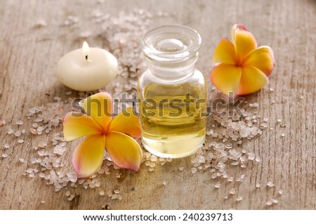 wooden background -frangipani, candle, oil and pile of salt