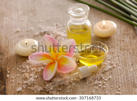 wooden background â??frangipani, leaf ,candle, oil and spoon pile of salt