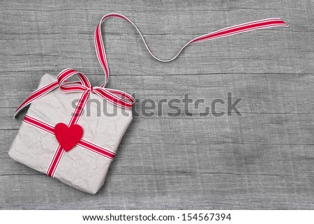 Wooden background with a present for christmas, valentine or birthday with a red heart - stock photo