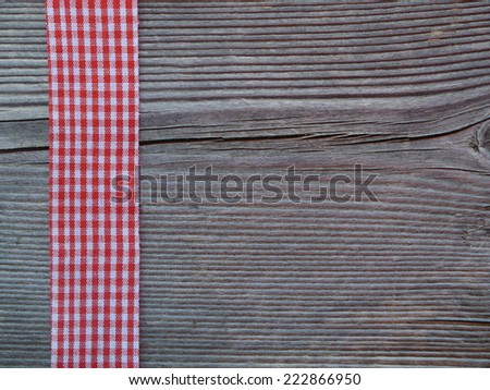 wooden background with a red checked ribbon - stock photo
