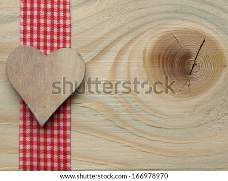 wooden background with a red checked ribbon and a heart - stock photo