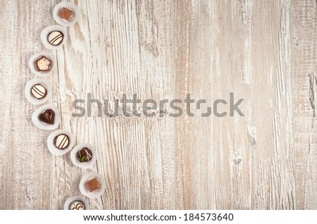 Wooden background with a row of chocolate pralines, text space - stock photo