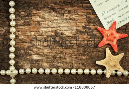 Wooden background with beads and starfish