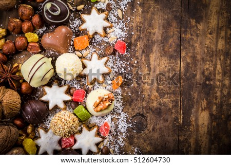 wooden background with candies, nuts, chocolate, dried fruits and other sweets, empty space for text