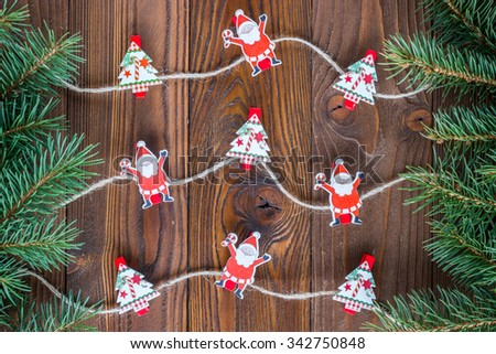 wooden background with Christmas tree and decoration as jute rope with decorative wood clothespins as fun Santa's and Christmas trees